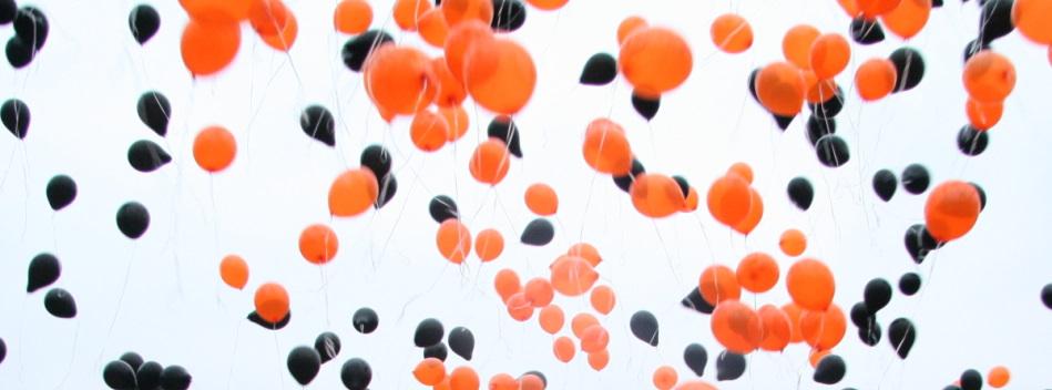 Steigende Luftballons in Kolpingfarben